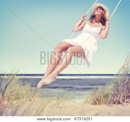 Beautiful Cheerful Woman Swinging by the Beach
