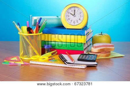 Pile of books, office supply, apple and sandwich