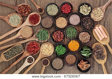 Large herb and spice selection in wooden spoons and bowls over oak wood background.