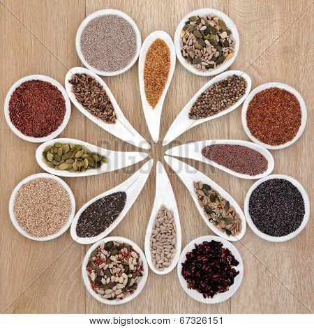 Large super food seed selection in porcelain bowls over light oak background.