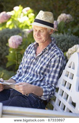 Mid age man reading newspaper in garden
