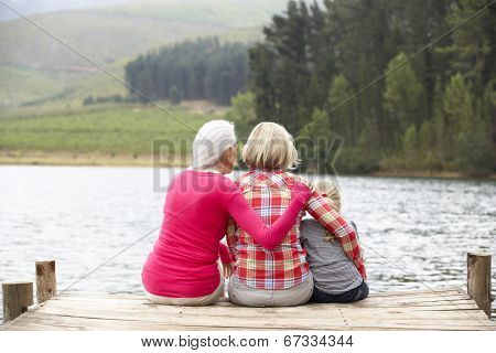 Mother, daughter and grandmother sitting on a jetty