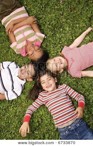 Kinder zusammen in Clover mit Köpfen liegen