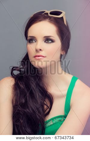 Portrait of a beautiful young brunette woman. Wearing retro sunglasses and loose curly hair. Open shoulders summer emerald green dress. Against grey studio background.