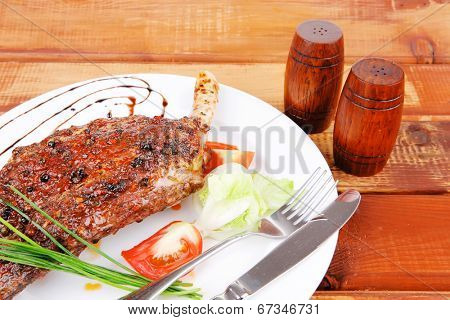 meat over wood: grilled shoulder on plate with tomatoes green lettuce and cutlery on white plate