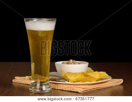 Glass of beer and snack on a black background