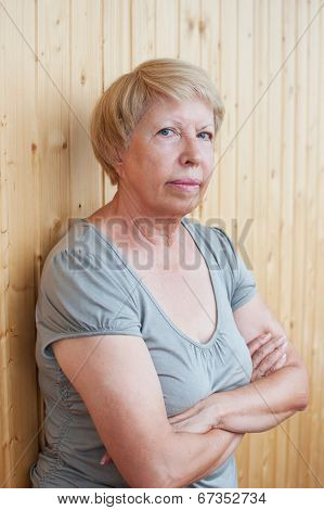 Portrait Of A Serious Middle-aged Woman On The Background Of Wooden Wall
