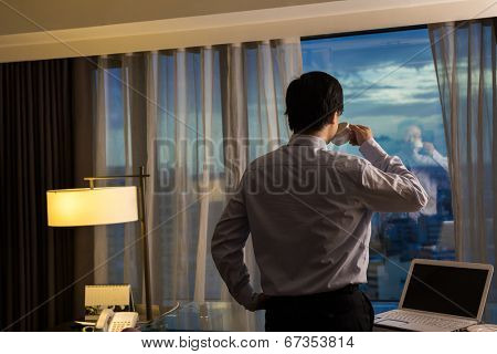 Asian businessman take a cup of coffee and looking into the distance, concept of traveling business, dream, work at night etc.