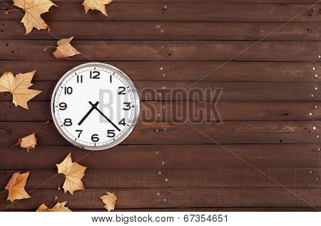 Clock With Leaves On A Brown Plank