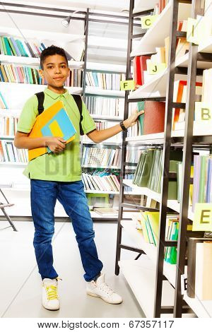 Standing boy with books in school library