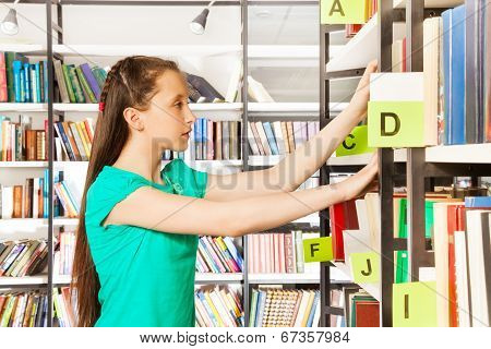 Girl with long hair searches book in library
