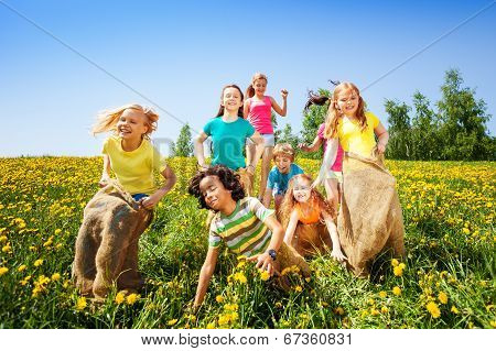 Cheerful children jumping in sacks play together