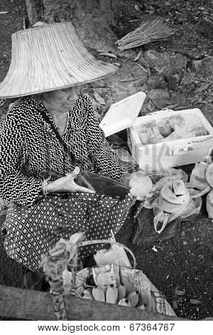 Old woman selling coconuts