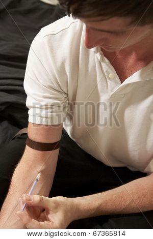 Teenage boy injecting drugs