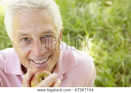 Senior man eating apple outdoors
