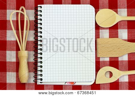 Notebook and wooden cooking utensils on red and white checkered tablecloth