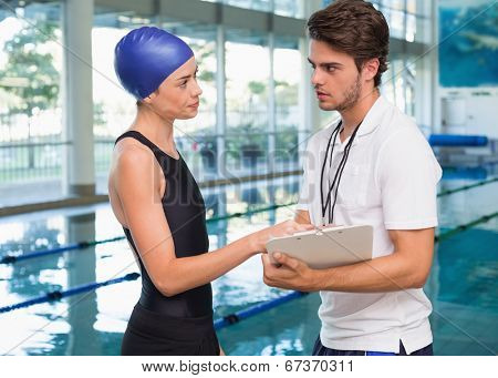 Swimmer discussing times with her coach by the pool at the leisure center