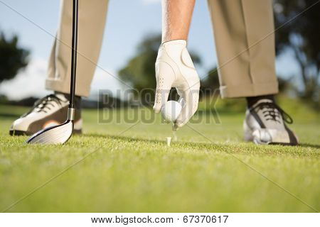 Golfer placing golf ball on tee on a sunny day at the golf course