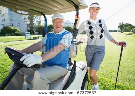 Happy golfing couple setting out for the day on buggy on a sunny day at the golf course