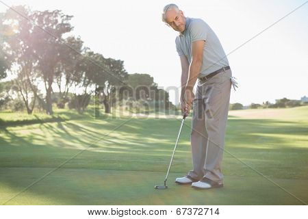 Handsome golfer putting ball on the green on a sunny day at the golf course