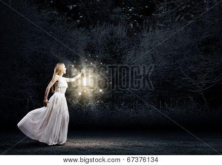 Young woman in white long dress walking in night wood