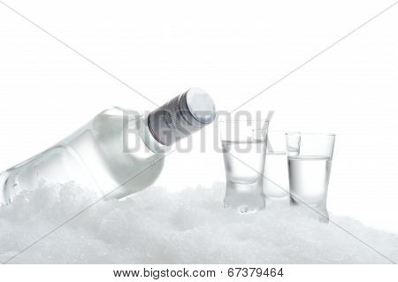 Bottle And Glasses Of Vodka Lying On Ice On White