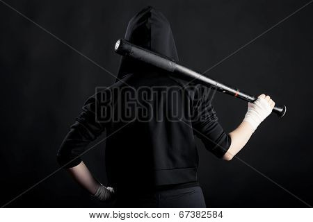 Young Woman With A Baseball Bat. View From The Back. Hoodlum