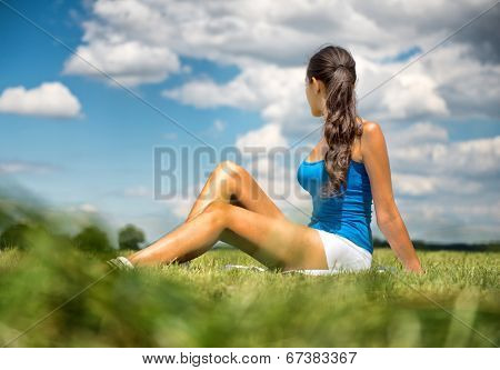 Tanned slender woman sitting in the grass in a green field looking away from the camera with her long brunette hair in a ponytail towards a sunny cloudy blue summer sky
