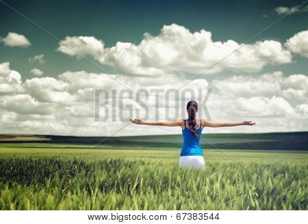 Toned dramatic image of a girl in a wheat field standing looking away from the camera with outspread arms as she rejoices her freedom and the beauty of the clouds and nature