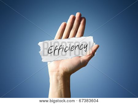 Man holding up a scrap of white paper with the word - Efficiency - in script, close up of his hand on a blue background with a side vignette in a conceptual image