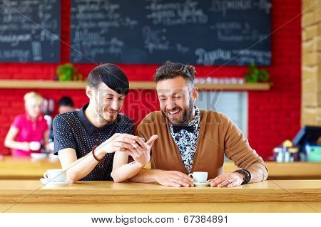 Two Male Friends Sitting In Cafe