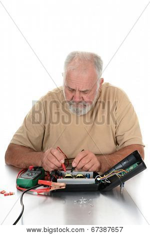 Closeup of a repairman using a voltmeter to test the components of an electrical device. The technician is looking down at his work. Vertical format over white.