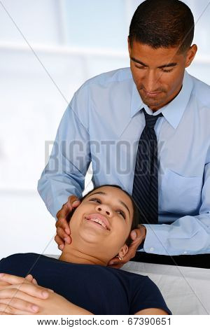 Male chiropractor working at his office with a patient