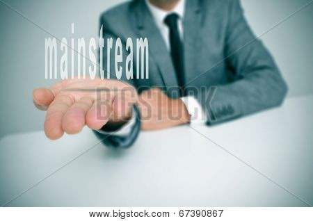 man wearing a suit sitting in a desk holding the word mainstream in his hands