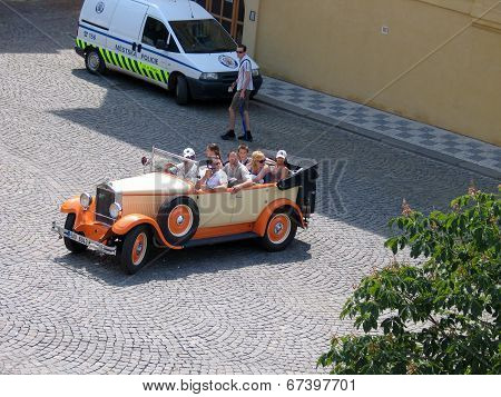 Prague, Czech Republic - June 15, 2006: Sightseers Make Trip At Old Town By Vintage Open Car On June