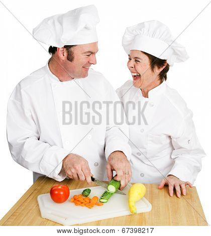 Two chefs working together in the kitchen and laughing as they cut up vegetables. Isolated on white.