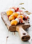 stock photo of melon  - Mozzarella prosciutto melon canapes on textured background - JPG