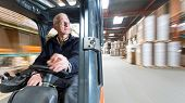 pic of forklift driver  - Elderly man driving a forklift through a warehouse where cardboard boxes are stored - JPG