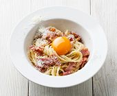stock photo of carbonara  - Pasta Carbonara on white plate with parmesan and yolk - JPG
