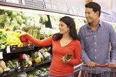 stock photo of supermarket  - Couple shopping in supermarket - JPG