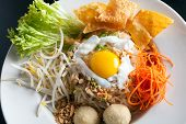 stock photo of gai  - Gai pad bai gaprow style Thai dish with fried egg and rice noodles - JPG