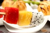 pic of fruit platter  - Platter of fruit skewers with a dish Healthy party food - JPG