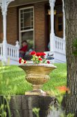 image of nebraska  - Red geraniums in an old stone pot sitting in front of a peaceful Nebraska home - JPG