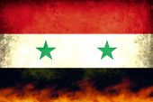 stock photo of revolt  - A damaged and burning Syria conflict flag - JPG