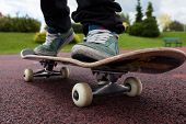 stock photo of skateboarding  - Young person rides on skateboard on court - JPG