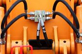 image of hydraulics  - Multiple Black Hydraulic Hoses on an Excavator Orange Industrial Detail - JPG