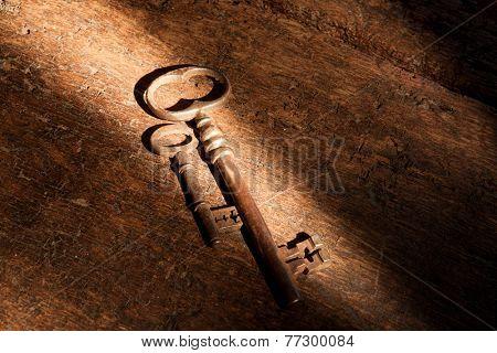 Light beam falling on rusty keys on very old wood