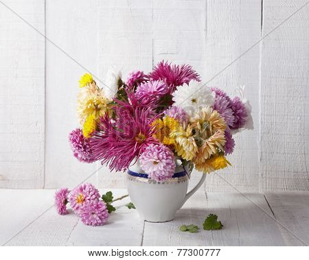 Still life with colourful chrysanthemums bunch on old white wooden board