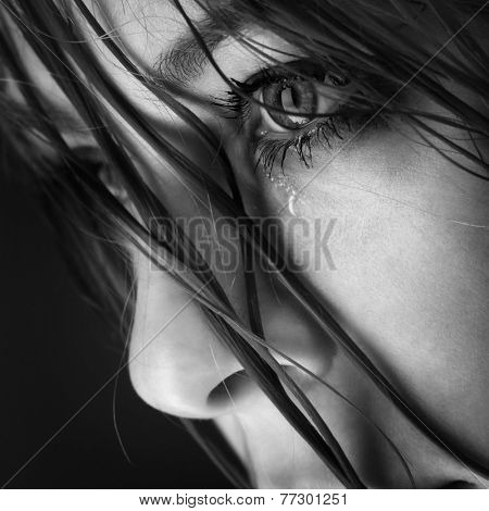 Beautiful girl crying against a black background.