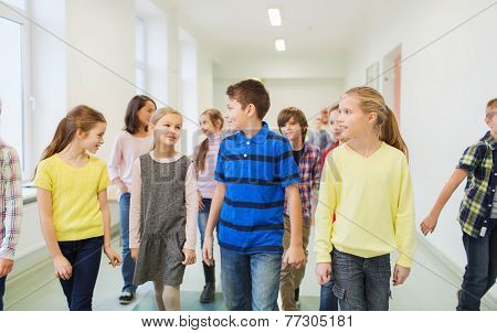 education, elementary school, drinks, children and people concept - group of smiling school kids walking in corridor